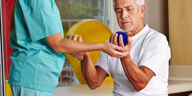 Senior mit Igelball bei Physiotherapie mit Physiotherapeutin